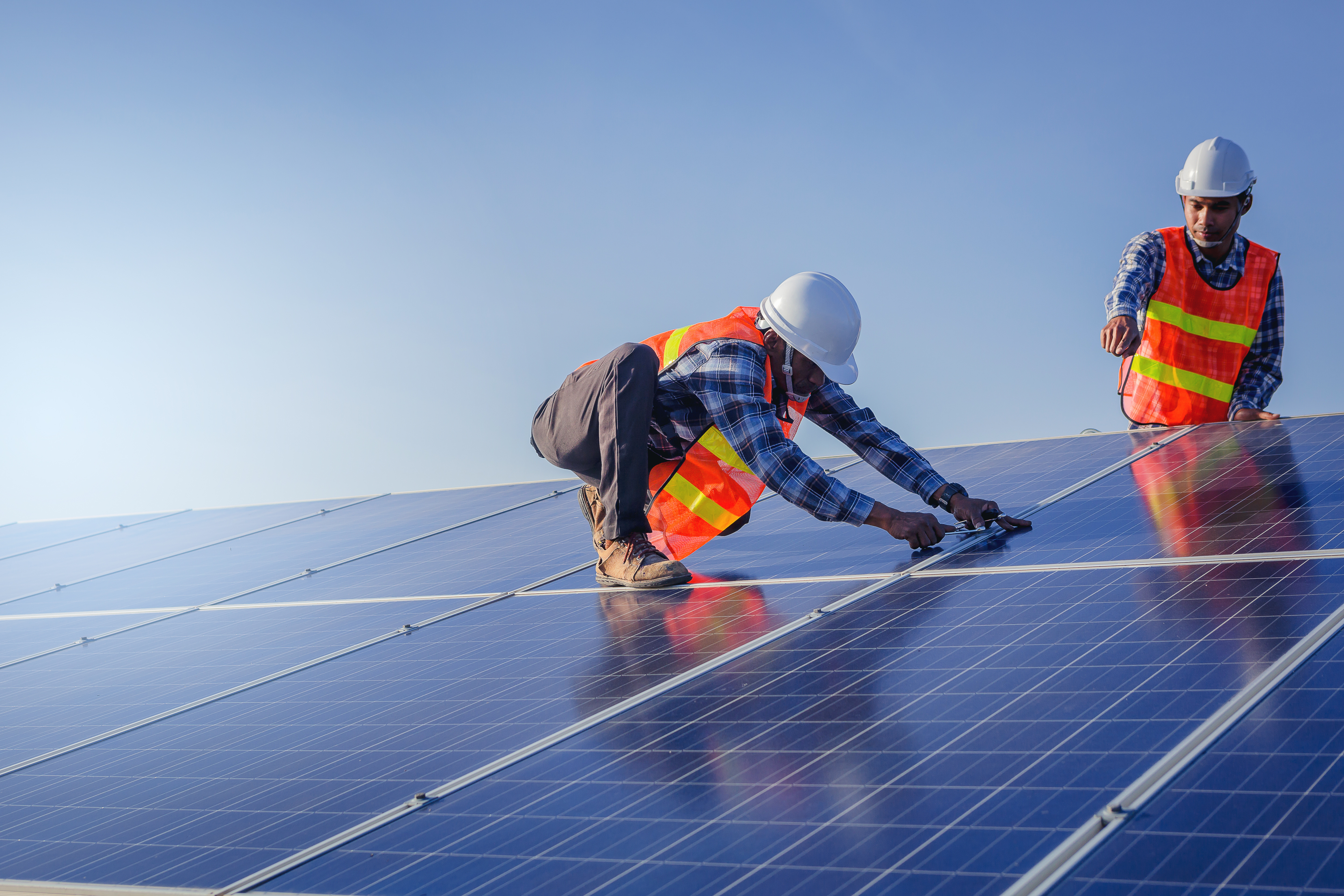 Solar Timeline: From Start To Finish; two people in orange work vests, installing solar panels